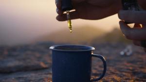 A person adding CBD Oil to coffee