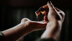 A woman putting a drop of CBD oil in her hand
