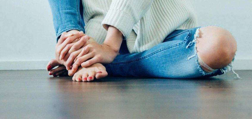 A woman experiencing foot pain is holding her foot